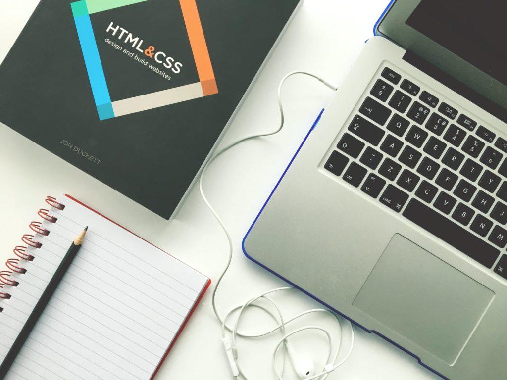 laptop i książka z instrukcja do tworzenia stron internetowych dla firm i koproacji